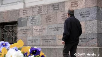 Ein Mann geht an der Mauer des KGB-Museums in Vilnius, in die Namen von Opfern eingemeisselt sind, entlang (Foto: DW/M.Griebeler)