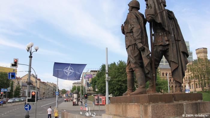 Statuen von Rote-Armee-Soldaten schauen auf der Grünen Brücke in Vilnius direkt auf eine riesige NATO-Flagge (Foto: DW/M. Griebeler)