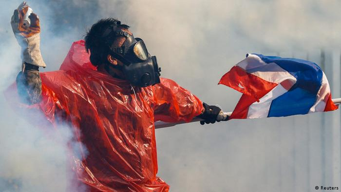 Thai protester hurling objects with flag and mask.