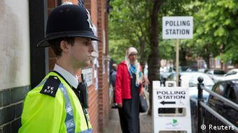 A policeman guards a pollling station in London