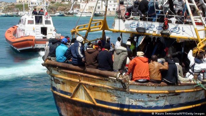Ein Boot voller Flüchtlinge fährt auf dem Mittelmeer und wird von der italienischen Küstenwache begleitet. (Foto: Mauro Seminara/AFP/Getty Images)
