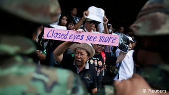 A woman holds a sign as she joins others in a protest against military rule in Bangkok May 24, 2014.