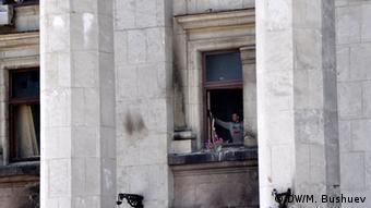Рабочий убирает георгиевскую ленту с окна в Доме профсоюзов, 24 мая 2014 года