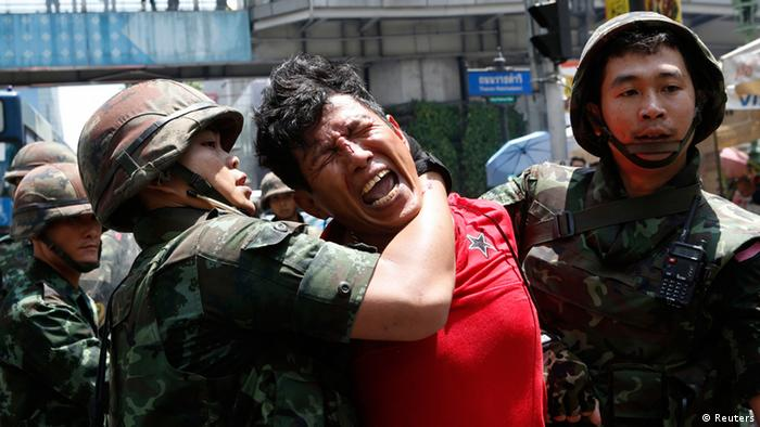A man cries with pain as he is arrested by a soldier in Thailand