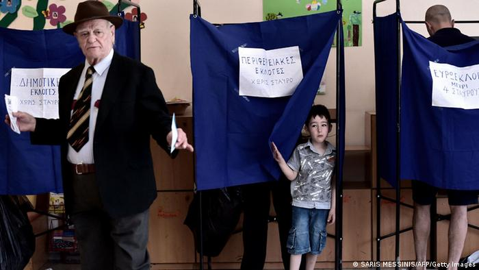 A young boy looks out from a voting booth during the European Parliament elections on May 25, 2014, at a polling station in Athens (Photo: ARIS MESSINIS/AFP/Getty Images)