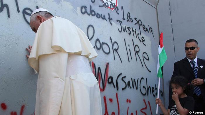 Pope Francis leans against the graffiti-covered separation wall, in prayer
