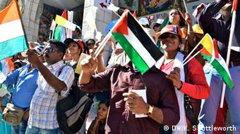 Palestinians waving flags by the roadside during the Pope's visit to Bethlehem