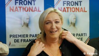 National Front leader Marine le Pen in front of election posters