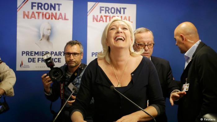 Le Pen smiling, flanked by a photographer