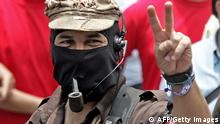 The leader of the Zapatista National Libertation Army (EZLN), Sub Comandante Marcos (C), flashes the 'v' sign as he takes part in a march along the streets of the Mexico City, 01 May, 2006 during the celebrations for May Day. From rural mountainous Nepal to the industrial heartland of Germany, workers took to the streets around the world on Monday in largely peaceful May Day demonstrations for labour rights, as immigrants in the United States prepared a jobs boycott. AFP PHOTO / Luis ACOSTA (Photo credit should read LUIS ACOSTA/AFP/Getty Images)