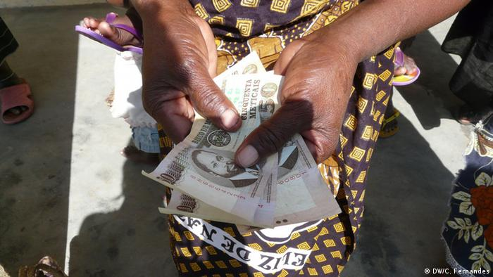Hands holding out Mozambican banknotes