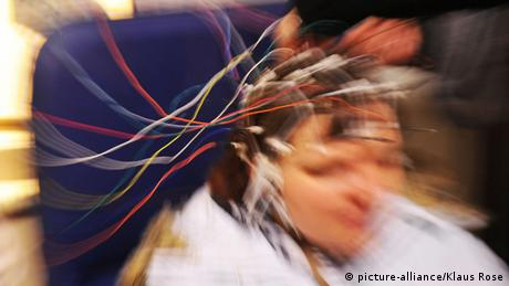 A blurred picture of a person with wires clipped onto their head
