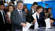 Ukrainian businessman, politician and presidential candidate Petro Poroshenko (L front) and his wife Maryna (R front), cast their votes during a presidential election at a polling station in Kiev May 25, 2014. Ukrainians voted on Sunday in a presidential election billed as the most important since they won their independence from Moscow 23 years ago, but armed pro-Russian separatists disrupted voting in eastern regions of the former Soviet republic. REUTERS/Gleb Garanich (UKRAINE - Tags: POLITICS ELECTIONS)