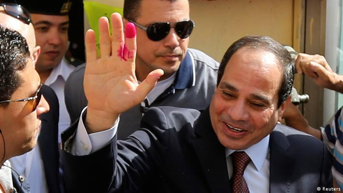 Al-Sisi holds up a red finger after voting