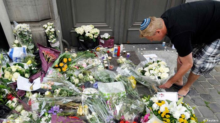 Man inspecting flowers laid before the Jewish Museum following the shooting. REUTERS/Belgian Police/Handout via Reuters