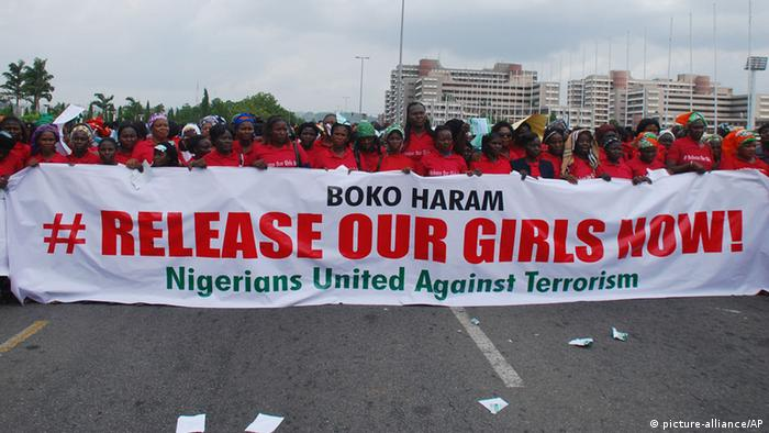 Nigerian protesters on the street holding banner calling for freedom of Chibok girls