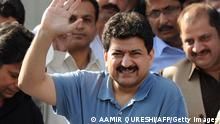Leading Pakistani TV journalist Hamid Mir, (C), who survived an April attack by gumen in Karachi, waves as he leaves the Supreme Court in a wheelchair after his appearance before the judicial commission in Islamabad on May 19, 2014. Journalists in Pakistan are under siege, Amnesty International warned, living with the constant threat of violence from intelligence agencies, armed groups such as the Taliban and even political parties. The shooting of Hamid Mir, the host of the primetime current affairs show Capital Talk on Pakistan's top-rating channel Geo, has led to a bitter row between the broadcaster and the military. AFP PHOTO/Aamir QURESHI (Photo credit should read AAMIR QURESHI/AFP/Getty Images)