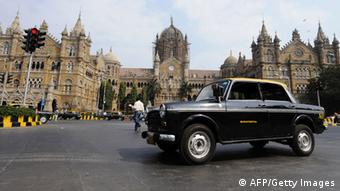 Ambassador - Compressed Natural Gas (CNG) taxis are driven past Chhatrapati Shivaji (Victoria) Terminus train station in Mumbai on January 27, 2009.
