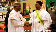Niger's newly elected president Mahamadou Issoufou (R) shakes hands with Hama Amadou, president of the Nigerien Democratic Movement (MDN), after taking the oath of office on the Koran during a ceremony on April 7, 2011 in Niamey. Mahamadou Issoufou appointed a member of the Tuareg community as prime minister, just hours after being sworn in and ending the period of military transition. Brigi Rafini, a Tuareg from Agadez in the north of the country, will lead the government, state radio announced. News of his appointment came just hours after Issoufou took his oath of office on the Koran, thus ending the military transition that began in February 2010 after the overthrow of Mamadou Tandja. AFP PHOTO / BOUREIMA HAMA (Photo credit should read BOUREIMA HAMA/AFP/Getty Images)