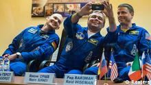 International Space Station crew member Maxim Surayev of Russia (C) takes a picture as fellow crew members Alexander Gerst of Germany (L) and Reid Wiseman of the U.S. look on during a news conference behind a glass wall at Baikonur cosmodrome May 27, 2014. The crew is scheduled to travel to the International Space Station on May 29. REUTERS/Shamil Zhumatov (KAZAKHSTAN - Tags: SCIENCE TECHNOLOGY)
