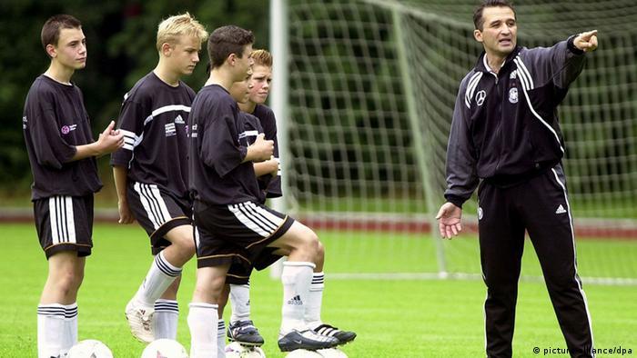 Trening juniora u doba prije korone (mladi igrači i trener na terenu)