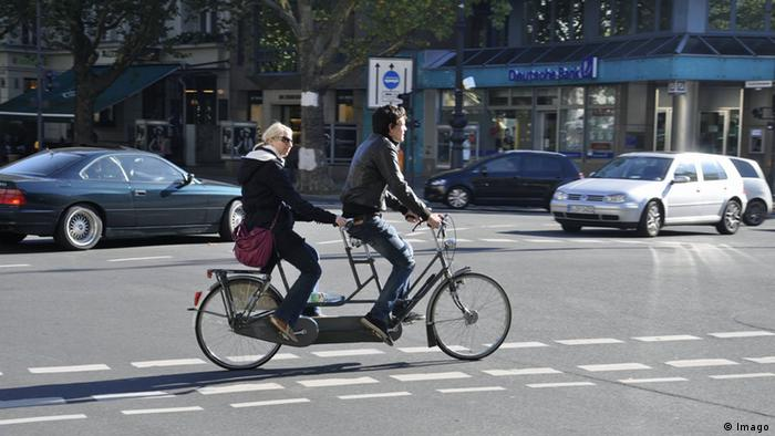 Two passengers ride a tandem bicycle in Berlin, Germany
