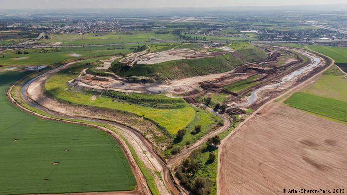 A large, multi-tiered, man-made hill being converted into a green space.