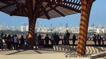 A large wooden canopy shades a lookout point with a view of downtown Tel Aviv