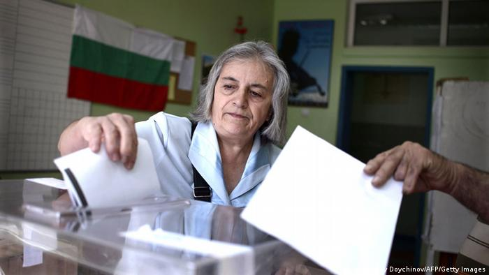 Женщина бросает бюллетень в избирательную урну на выборах в Болгарии