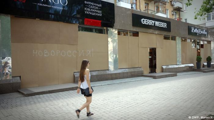 People walk past boarded up shops in the center of the city.