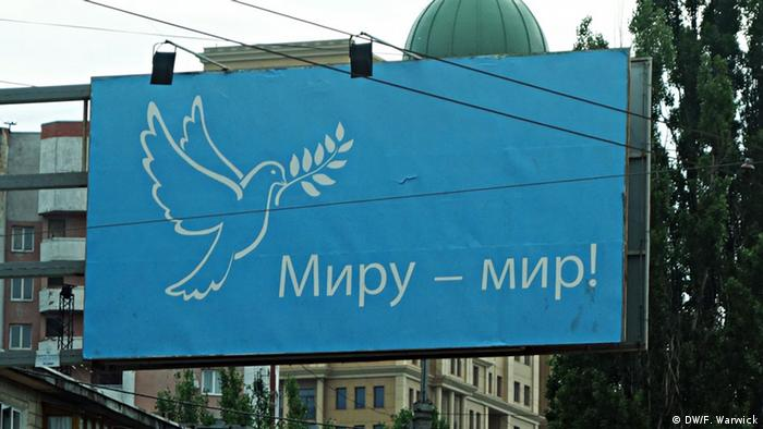 Billboards calling for peace to the world with a white dove on a blue background can be found around the city.