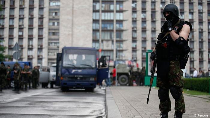 An armed pro-Russian separatist stands guard on a street outside the regional administration building in the east Ukrainian city of Donetsk (Photo: REUTERS/Maxim Zmeyev)