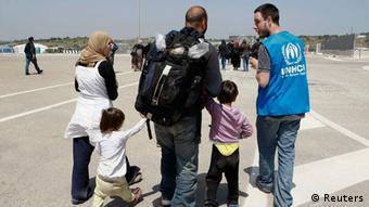 Eine syrische Familie wird in einem italienischen Hafen von einem Mitarbeiter der Flüchtlingsorganisation UNHCR in Empfang genommen und begleitet. (Foto: Reuters/Antonio Parrinello)