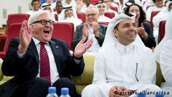 Frank-Walter Steinmeier laughing and clapping during a visit in Qatar