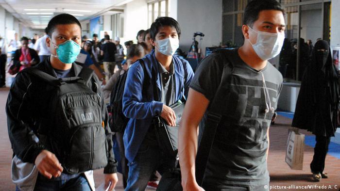 چند کارگر فیلیپینی که از خاورمیانه به کشور خود بازگشتهاند برای رعایت مسائل بهداشتی ماسک تنفسی استفاده میکنند