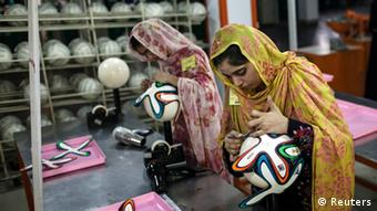 An employee adjusts outer panels on a soccer ball inside the soccer ball factory that produces official match balls for 2014 World Cup in Brazil, in Sialkot, Punjab province May 16, 2014 (Photo: REUTERS/Sara Farid)