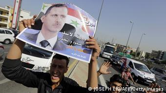 man holding poster JOSEPH EID/AFP/Getty Images