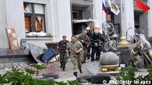 Pro-Russian militants and firemen run away as they leave the Regional State building they seized during a shoot-out with Ukrainian border guards defending the Federal Border Headquarters building in the eastern Ukrainian city of Lugansk on June 2, 2014. Ukrainian forces killed five rebels on June 2 while repelling an attack by 500 pro-Russian gunmen on a federal border guard camp in the strife-torn separatist east, Kiev officials said. The border guard service said seven of its servicemen were wounded when around 500 terrorists attacked one of its units stationed outside the industrial city of Lugansk. AFPPHOTO/ ALEX INOY (Photo credit should read ALEX INOY/AFP/Getty Images)