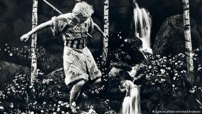 Film still 'Die Nibelungen': actor Paul Richter jumping in a field of flowers