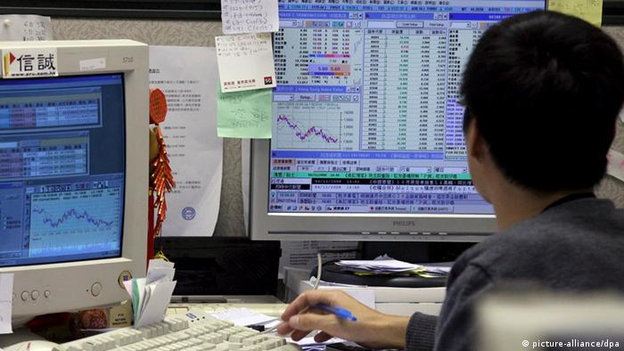 An investor checks stocks price at a securities firm in Hong Kong