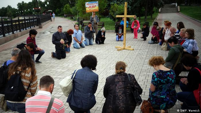 Inter-faith prayer meeting by the river in Donetsk. Copyright: DW / Filip Warwick