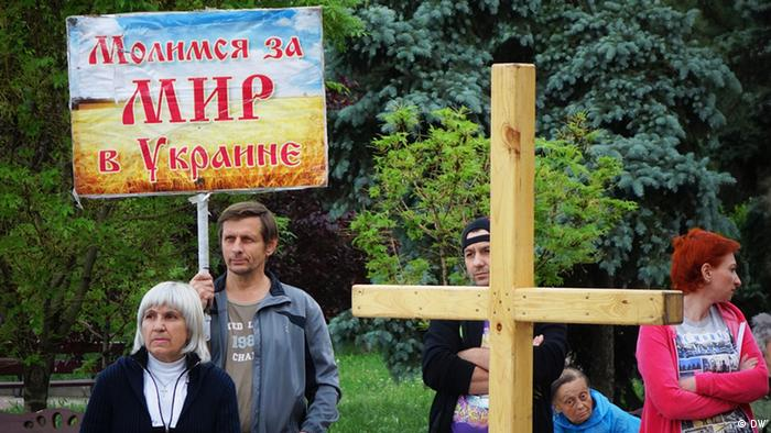 A close up showing a corss and some signs at the Inter-faith prayer meeting in Donetsk. Copyright: DW / Filip Warwick