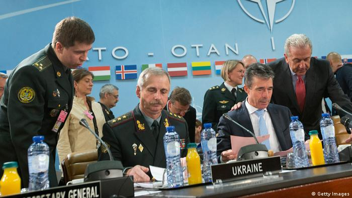 Acting Defense Minister for Ukraine Col. Gen. Mykhailo Koval, left seated and NATO Secretary General Anders Fogh Rasmussen, right seated, take their seats before the start of their meeting at North Atlantic Council (NATO) at NATO headquarters on June 3, 2014 in Brussels, Belgium. NATO defense ministers are meeting for the first time since the crisis in Ukraine and will consider their response to Russia's military occupation and annexation of Crimea. (Photo by Pablo Martinez Monsivais - Pool/Getty Images)