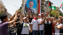 Supporters of of Syria's President Bashar al-Assad celebrate in front of a polling centre in Damascus June 3, 2014. Syrians voted on Tuesday in an election expected to deliver an overwhelming victory for al-Assad but which his opponents have dismissed as a charade in the midst of Syria's devastating civil war. REUTERS/Khaled al-Hariri (SYRIA - Tags: POLITICS CIVIL UNREST ELECTIONS)