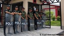 Police officers with shields guard the entry to a Peruvian courthouse
