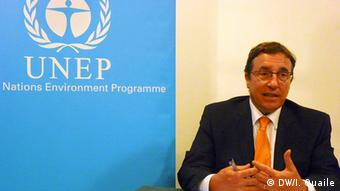 A man in a business suit in front of a blue poster which reads UNEP