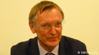 Janez Potocnik smiles off-camera in front of a beige backdrop