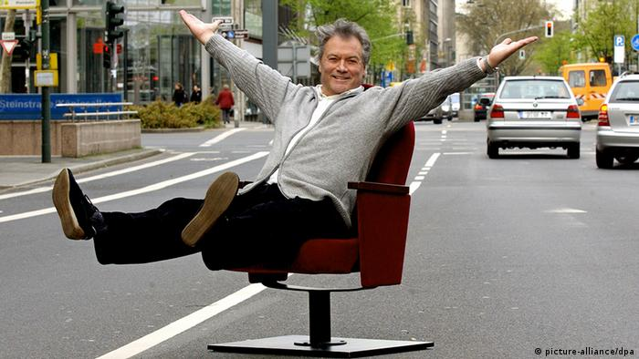 Hans-Jürgen Bäumler sitting on a chair in the middle of the street