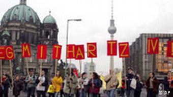 Demonstranten halten Plakate, die den Schriftzug Weg mit Hartz IV ! ergeben, waehrend einer Demonstration gegen die neue Bundesregierung in Berlin am Samstag, 5. November 2005
