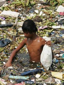 Eine Junge steht hüfttief in schwimmendem Müll (Foto: China Photos/Getty Images)